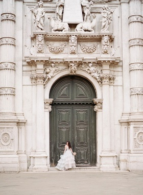 Bride in Hayley Paige wedding dress in front of historic building door columns carvings sculpture