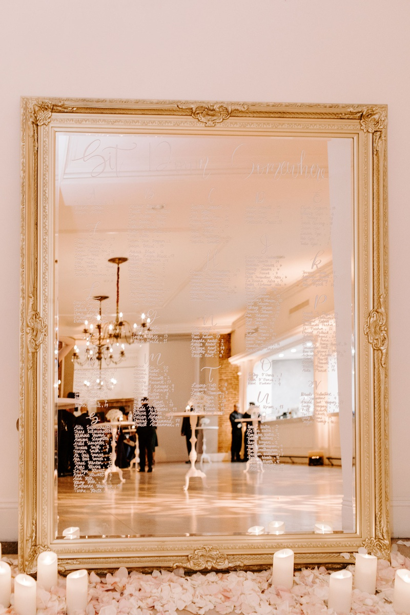 gold framed mirror seating chart, pillar candles, rose petals on floor