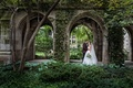 Bride in strapless wedding dress and veil with groom in maroon suit tuxedo ivy on building church