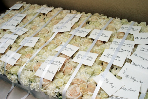 White escort card under ribbon on rose bed