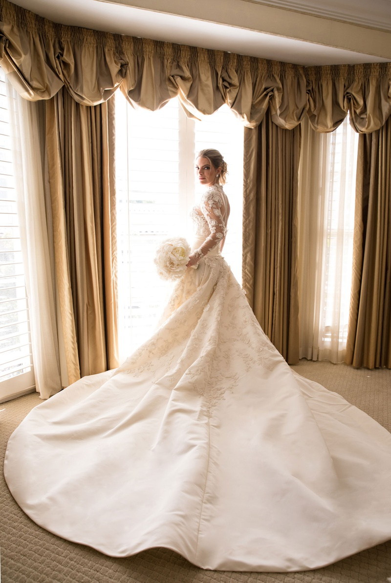 Bride in marchesa couture wedding dress high neck illusion long sleeves long train white bouquet