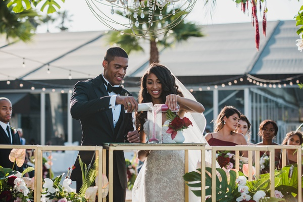 bride and groom pouring different colored sand into canister, wedding unity ceremony ideas