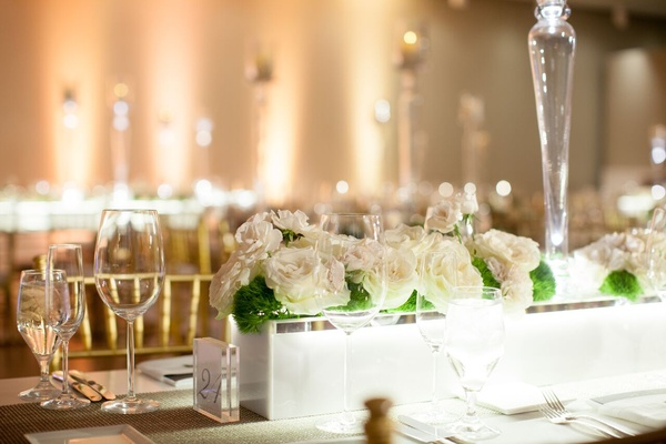 marble planters with white roses at modern museum wedding reception