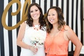 Bride in white dress and coral necklace, white rose bouquet at bridal shower