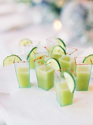 Geometric shot glasses filled with cucumber gazpacho green soup smoothie with red rim
