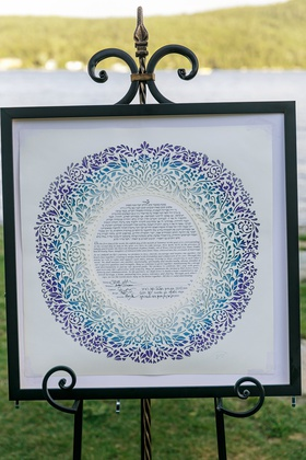 ketubah displayed at ceremony, ketubach with laser-cut vine patterns in shades of blue