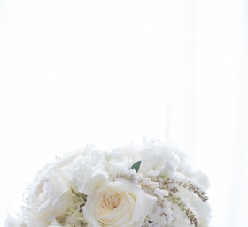 Bride's bouquet of white flowers including garden roses tied with lace like in the bride's dress
