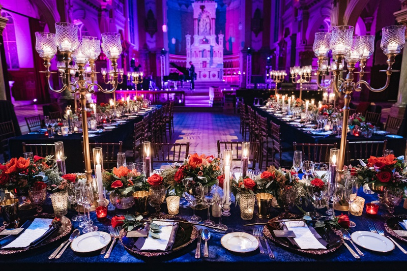 wedding reception bright purple blue lighting gold candelabra blue linen red flowers candlelight