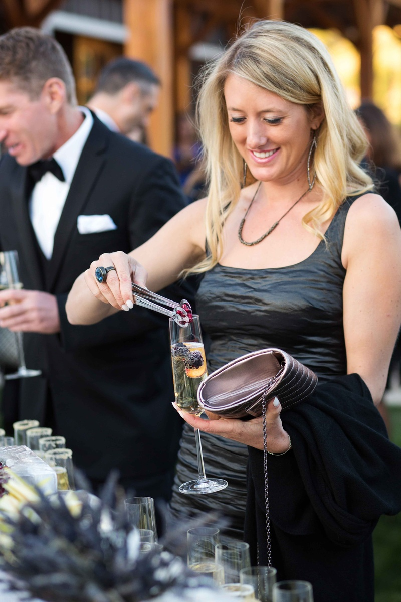 Wedding guest adding raspberry, blackberry, and peach to Champagne flute garnish