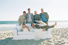 Bride and groom with family on white sofa on beach