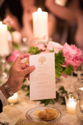 guest holds printed dinner menu for wedding reception with gold print and tree design