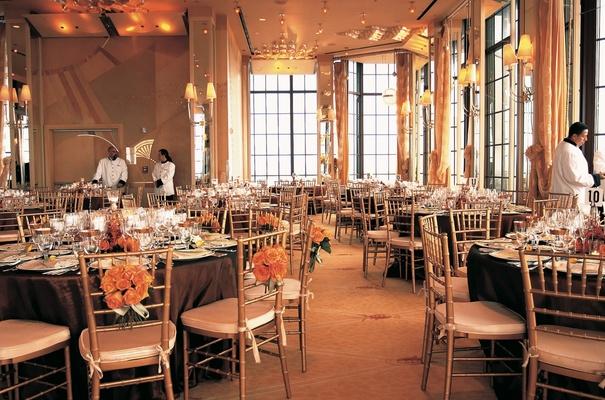 Wedding reception ballroom decorations in gold, orange, and peach
