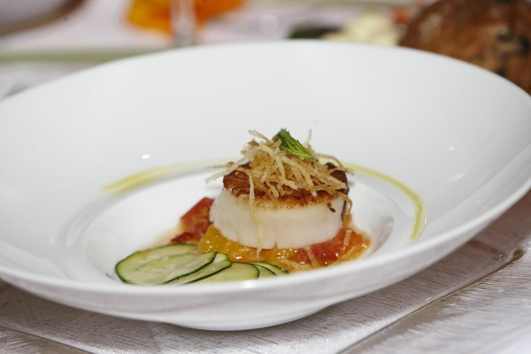 Scallop on bed of yellow and orange sauce