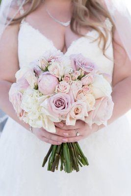 bride in v neck ball gown with necklace carrying blush lavender ivory bouquet of rose peony flowers