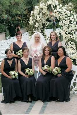 Long purple bridesmaids dresses with matching wraps and green, white, and purple bouquets