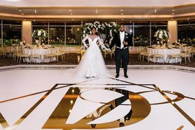wedding reception portrait of bride and groom gold foil dance floor tables perimeter ballroom