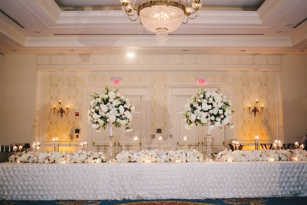 Two flower centerpieces on top of long reception table