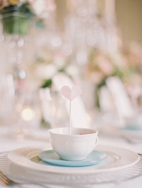 Heart-shaped place card propped inside a teacup
