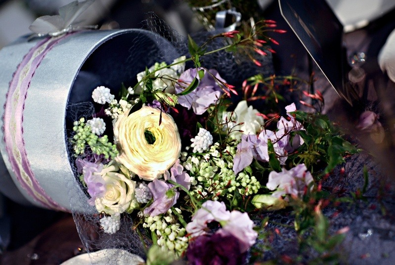 Wedding reception floral arrangement of yellow, white, light purple, and red flowers