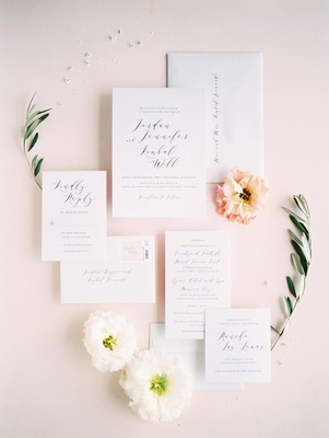 wedding invitation suite detail shot with flowers pink white greenery flower petals stamps minted