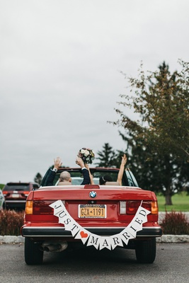 "bride and groom with arms raised in vintage red BMW convertible with ""just married"" banner"