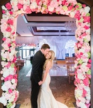 bride in romona keveza, groom in suit, newlyweds pose in pink floral frame of hydrangeas