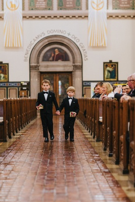 two ring bearers in tuxedos holding hands, two ring bearers each with a ring box