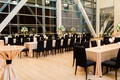 clinton presidential library wedding, black chairs, long tables, gold linens, large windows