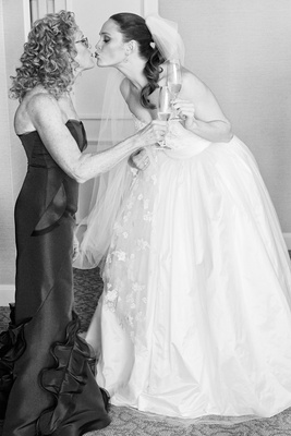 Black and white photo of bride in ball gown kissing mother of bride in strapless gown champagne