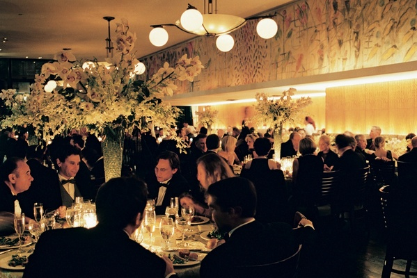 Guests in black tie around wedding reception tables in New York