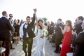 Bride in Monique Lhuillier wedding dress and groom hold hands celebrate after getting married aisle