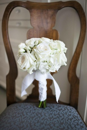 Ivory flowers wrapped in scalloped ribbon on chair