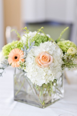 Wedding reception centerpiece of white hydrangea, pastel orange gerbera daisy, greenery