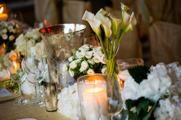 Wedding reception table decorated with white flowers, candles and mercury vessels