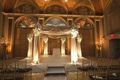 Chuppah draped in light golden fabric decorated with white and blue flower arrangements