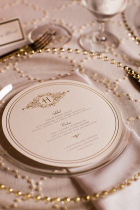round wedding menu with double lined border and embellished monogram on top, clear charger with gold