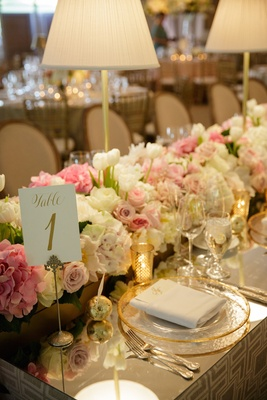 Wedding reception table with a mirror top, table number written in gold ink, white roses, tulips,