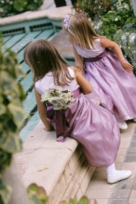 Flower girls wearing light purple dresses with dark purple sashes