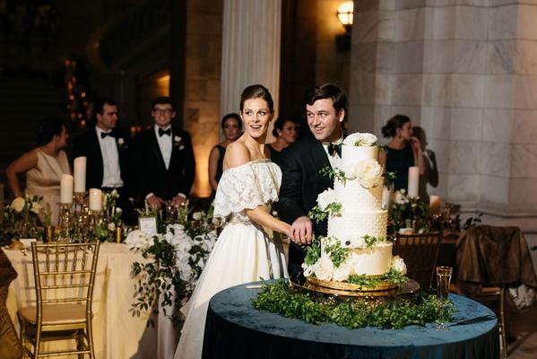 bride in lace off shoulder wedding dress mom's dress groom cutting classic wedding cake design