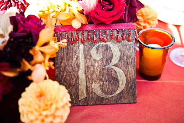 Wedding reception table number on a wood board decorated with red ribbon and beads