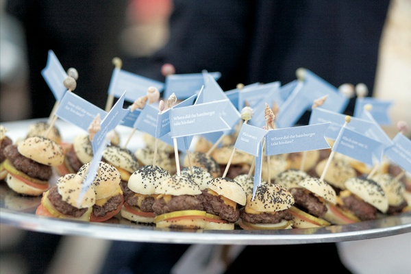 Miniature cheeseburgers with light blue flags