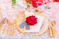 Wedding table with texture linen, gold flatware, gold rim charger, red rose, black and white ribbon