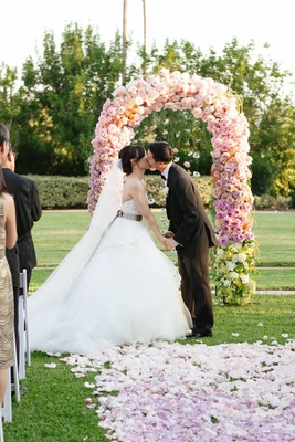 floral arch and aisle covered in pastel flowers arranged in ombre pattern
