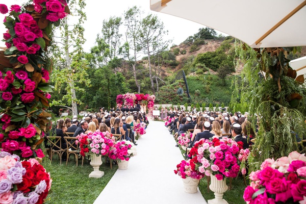 outdoor jewish wedding ceremony bright pink rose magnolia leaves lavender white aisle vineyard chair