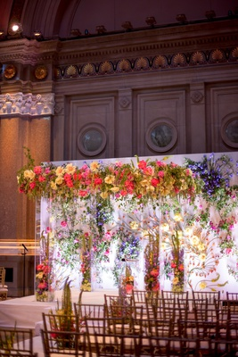 Wedding ceremony with colorful vibrant flowers in chuppah lucite column backdrop