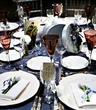 Wedding reception table with blue tablecloth, white tableware, and red glassware