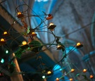 green wire molded into triangle shaped chandeliers with votives