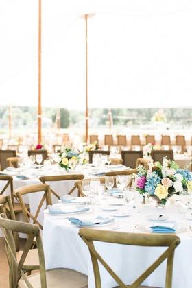 Wedding reception round table white linen wood chair cross back x blue napkin low centerpiece flower