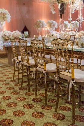 Gold amber wedding chairs with ivory cushions tied around mirror long rectangle table