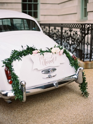 Wedding ceremony just married getaway car with wreath garland and fresh flowers on back classic car